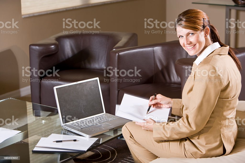 Businesswoman sitting in hotel lobby working on laptop and paper stock photo