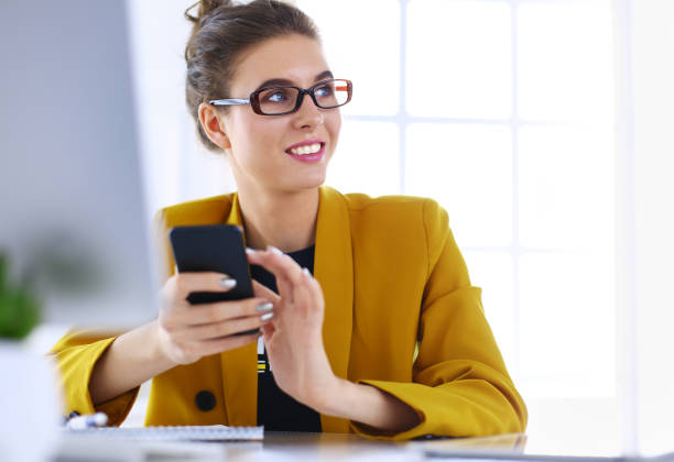 Geschäftsfrau sitzt im Büro mit Laptop am Telefon – Foto