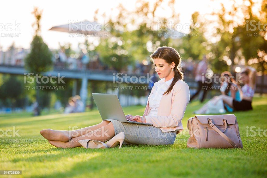 Businesswoman sitting in park working on laptop, sunny summer da stock photo