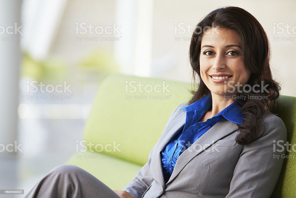 Businesswoman sitting on a green sofa in a modern office stock photo