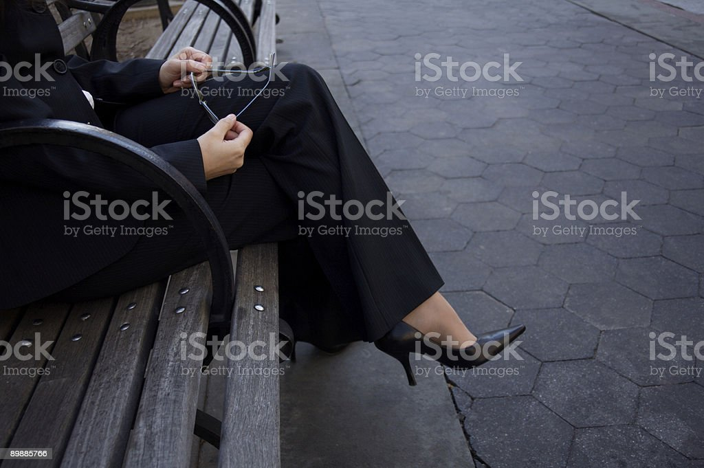 Businesswoman sitting on a park bench and holding eyeglasses royalty-free stock photo
