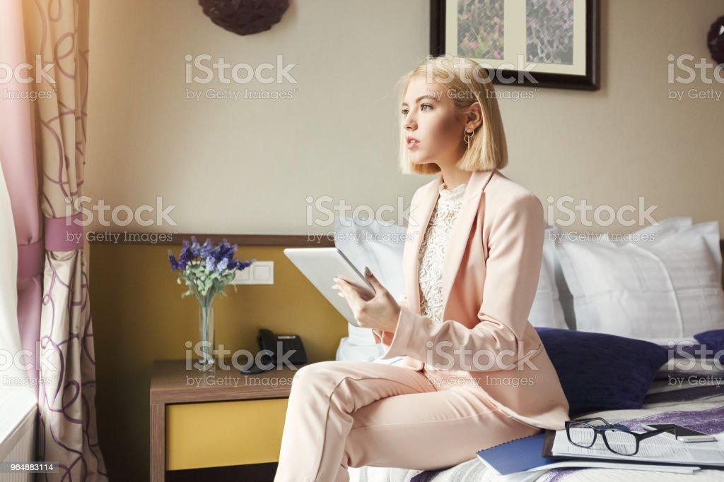 女商人坐在床上使用平板電腦 - 免版稅一個人圖庫照片