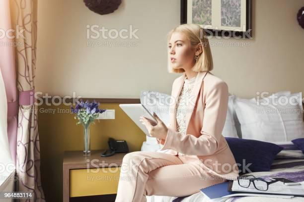 女商人坐在床上使用平板電腦 照片檔及更多 一個人 照片