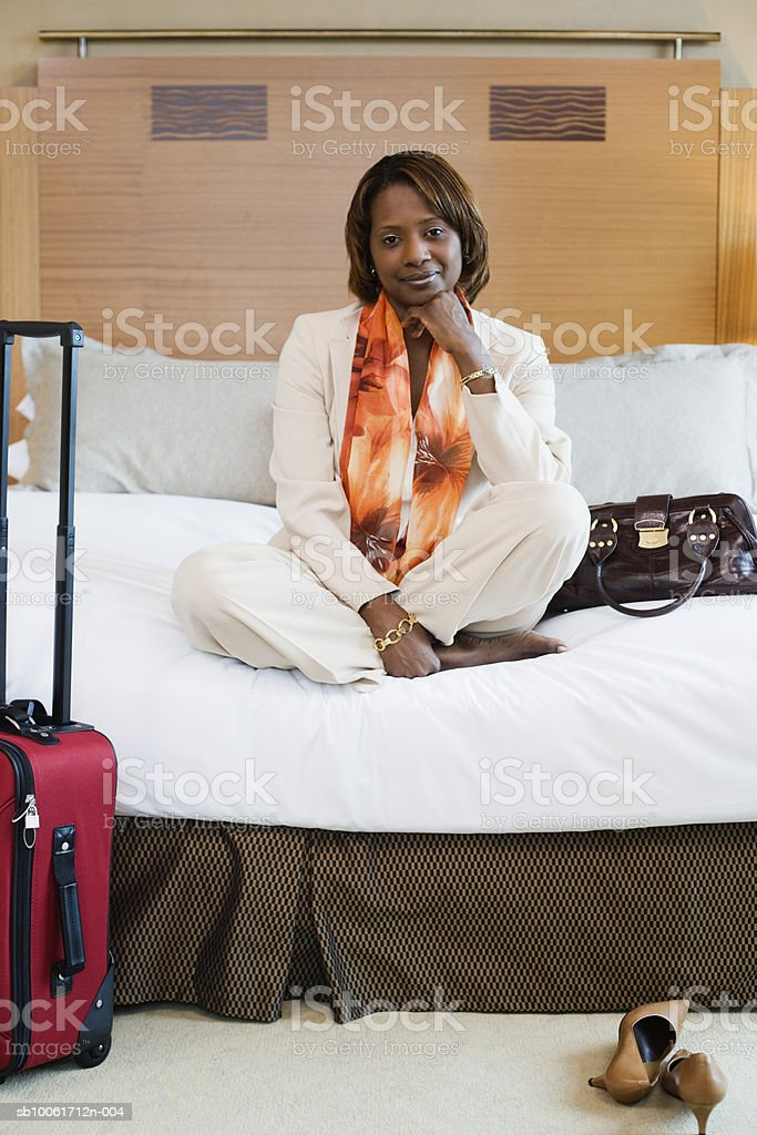 Businesswoman sitting on bed in hotel room, smiling royalty free stockfoto