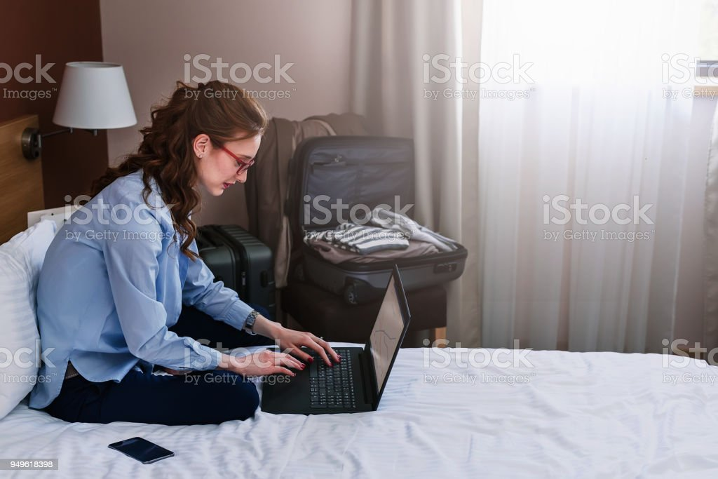 Businesswoman sitting on bed, using laptop. Woman working in hotel room stock photo