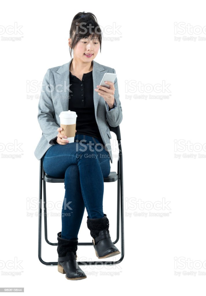 Businesswoman sitting on chair and using phone stock photo