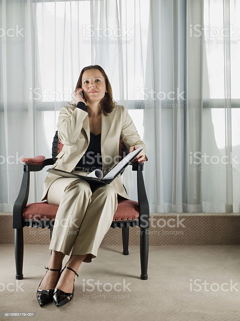 Businesswoman sitting on chair, looking up, using mobile phone royalty-free 스톡 사진