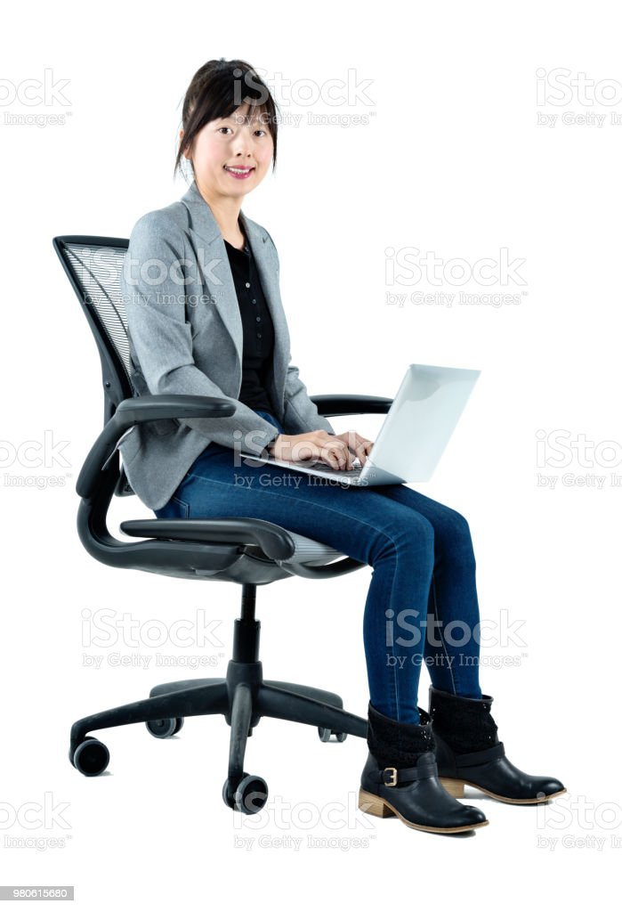 Businesswoman sitting on chair with a laptop stock photo