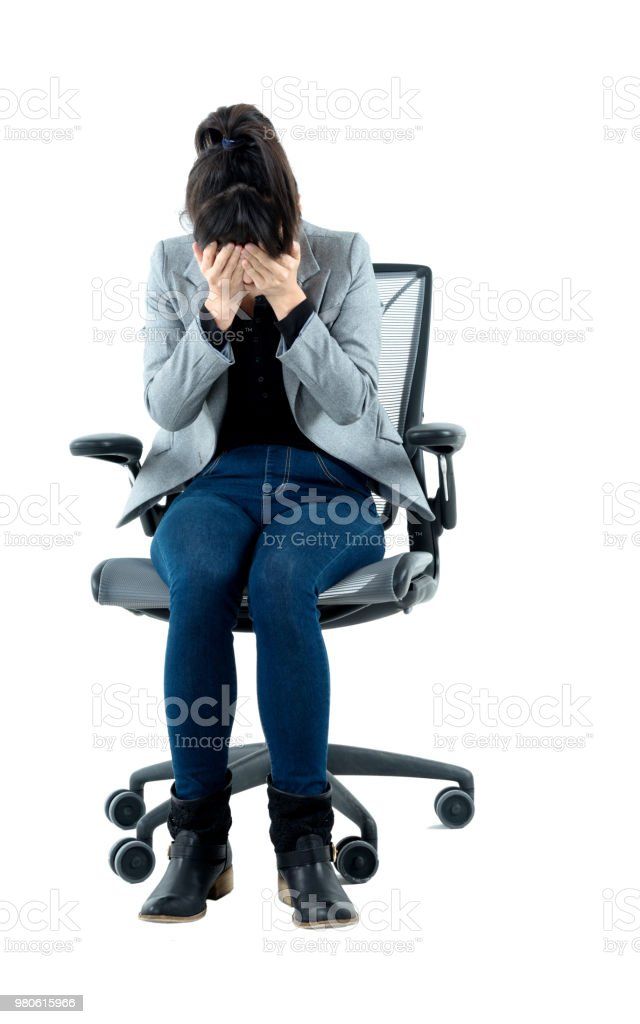 Businesswoman sitting on office chair and covering her face stock photo