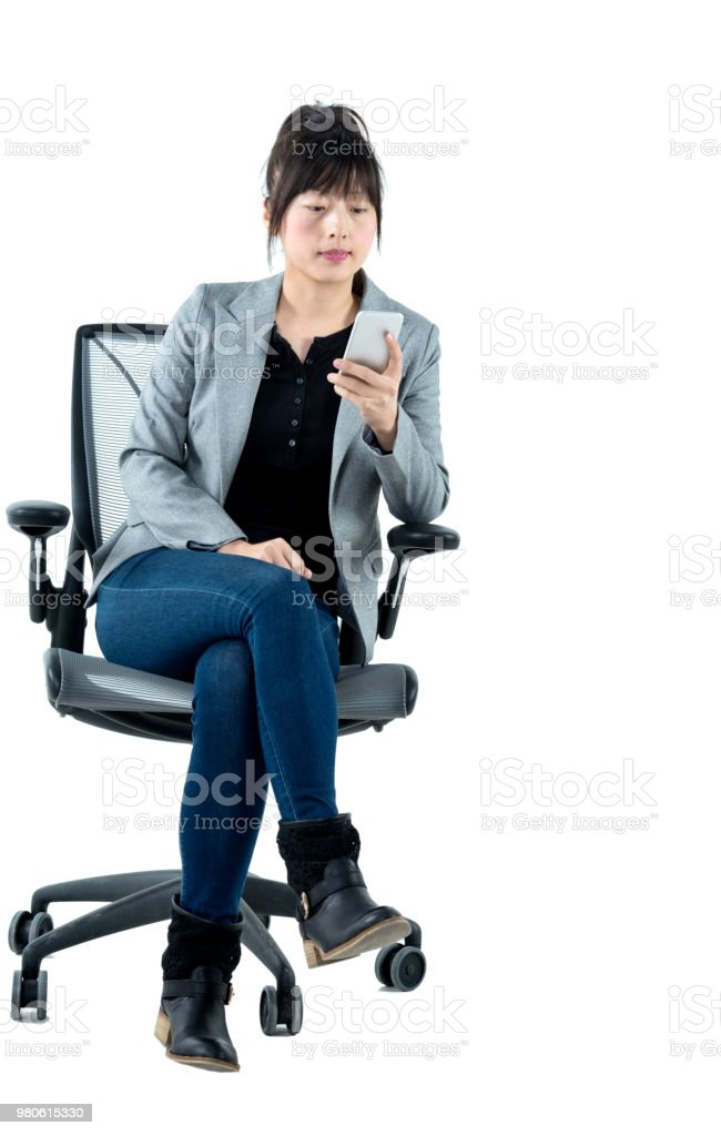 Businesswoman sitting on office chair and using phone stock photo
