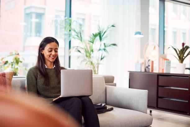 坐在辦公桌上的辦公桌上工作的女商人在共用工作空間辦公室的辦公桌上工作 - 虛擬辦公室 個照片及圖片檔