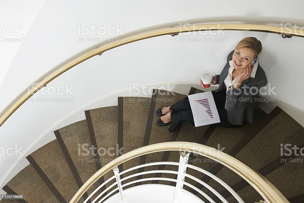 Businesswoman Sitting On Stairs Using Mobile Phone royalty-free stock photo