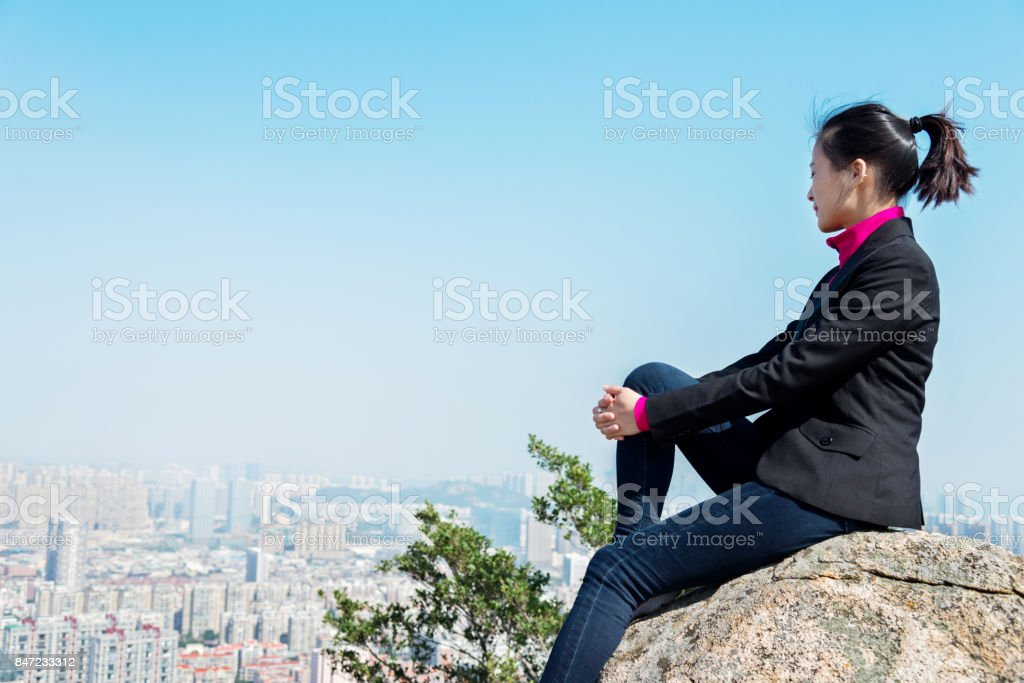 Businesswoman sitting on top of the mountain stock photo