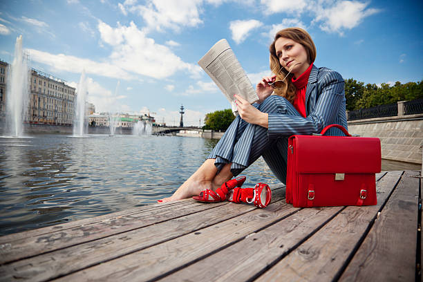 Geschäftsfrau im Freien sitzen und lesen Zeitung – Foto