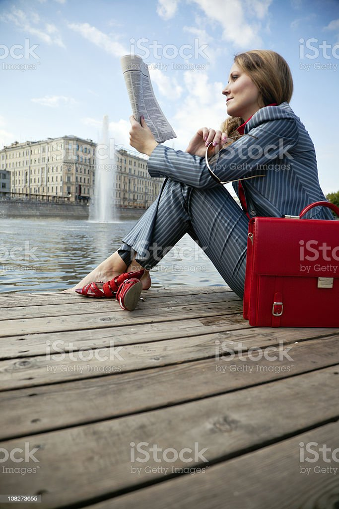 Businesswoman sitting outdoors and reading newspaper royalty-free stock photo
