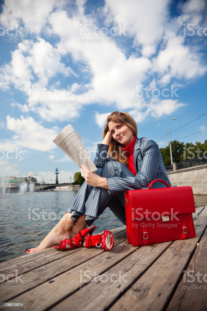 Деловая женщина, сидящая на открытом воздухе и чтение газеты стоковое фото