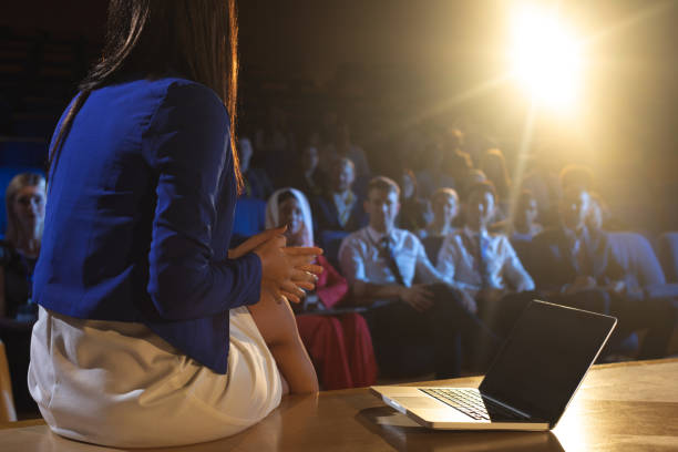 Businesswoman sitting with a laptop and discussing with the audience Rear view of beautiful businesswoman sitting with a laptop and discussing with the audience speech stock pictures, royalty-free photos & images