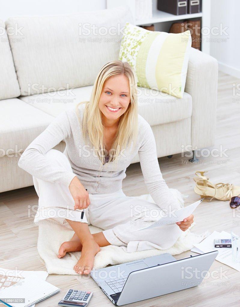 Деловая женщина, сидящая с ноутбуком и документами в дом стоковое фото