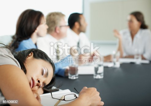 istock Businesswoman sleeping in conference room during meeting 85406832