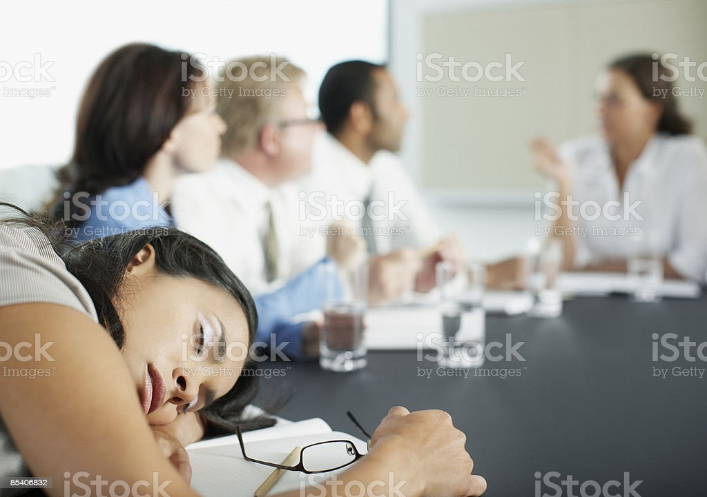 Businesswoman sleeping in conference room during meeting stock photo