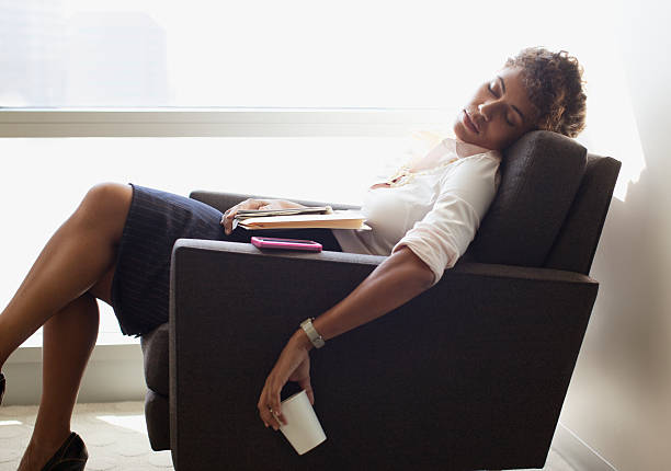 Businesswoman sleeping in office chair stock photo