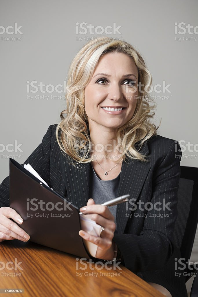 Businesswoman smiles while holding documents royalty-free stock photo
