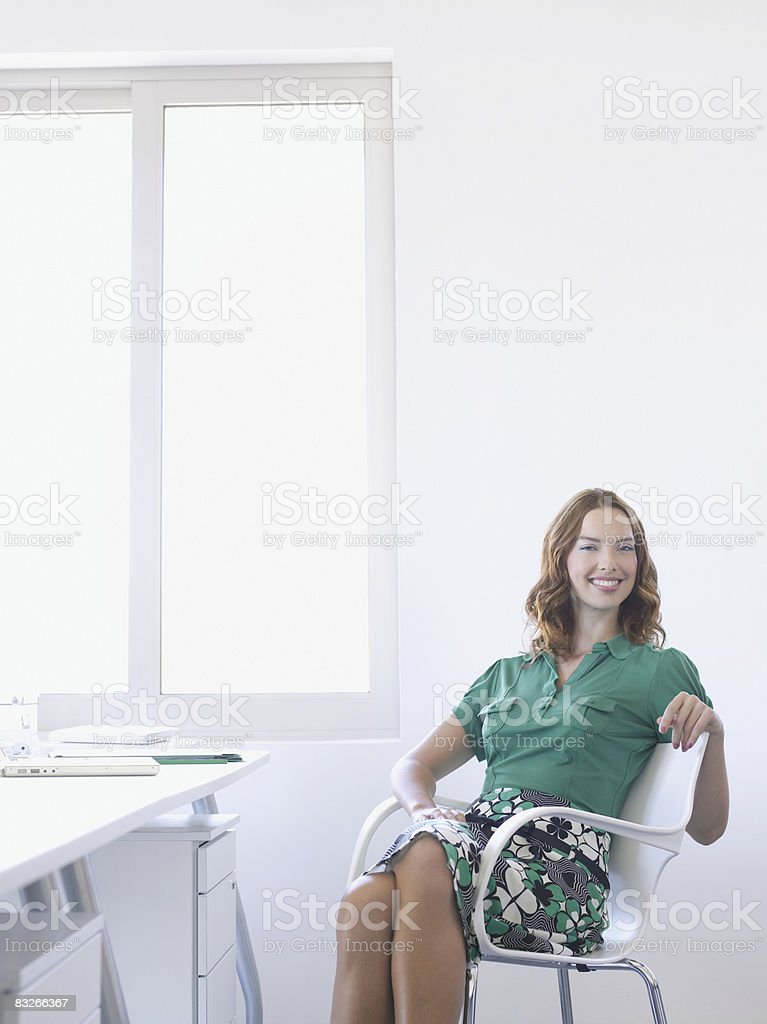 Businesswoman smiling at desk royalty free stockfoto