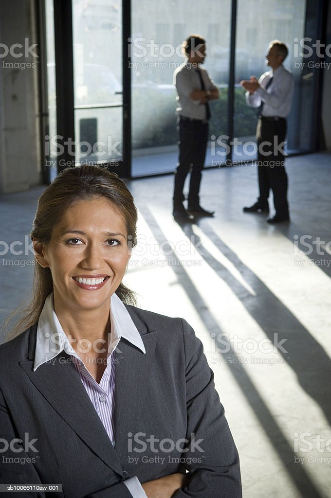 Businesswoman smiling, colleagues in background foto de stock libre de derechos