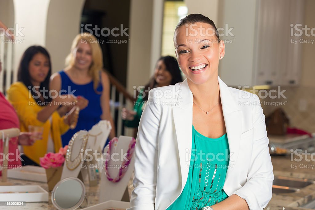Businesswoman smiling during direct sales home jewelry party stock photo
