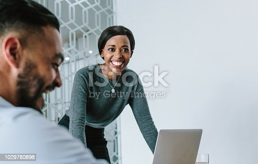 Businesswoman standing by her laptop and smiling during a board room meeting. Smiling woman giving presentation to her team in conference room.