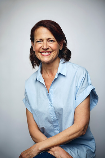 Portrait of businesswoman smiling. Confident executive is wearing blue shirt. Female professional is smiling over white background.