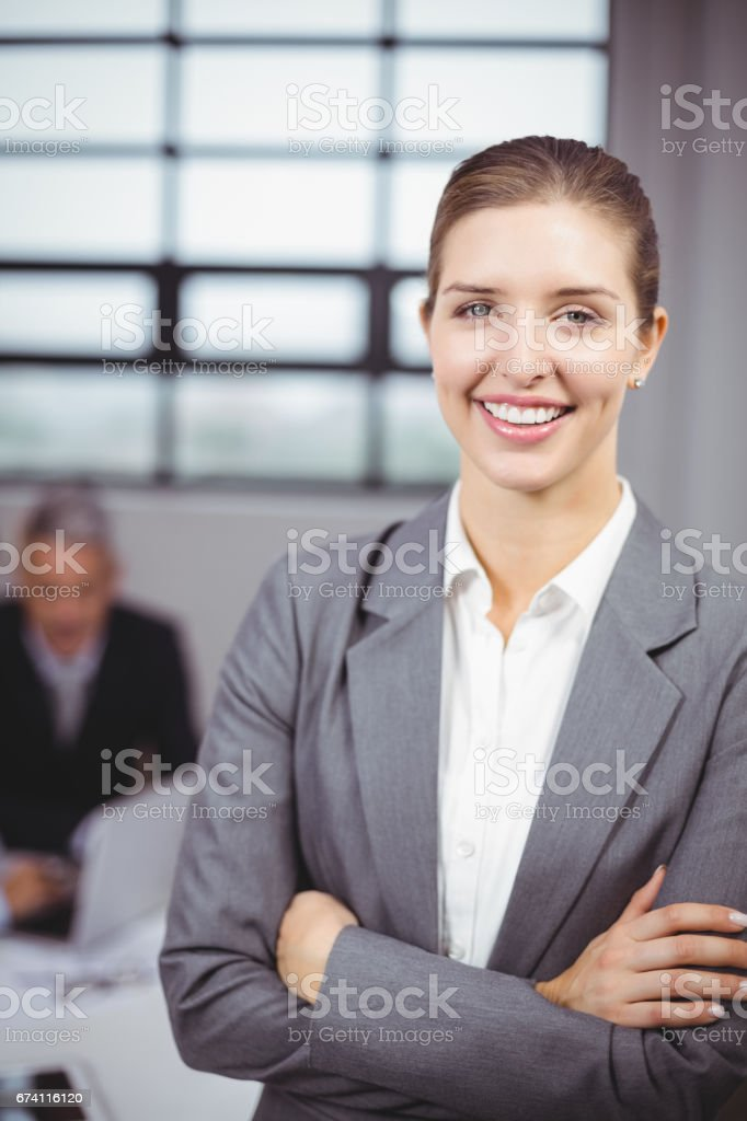 Businesswoman smiling while business people in background royalty-free stock photo