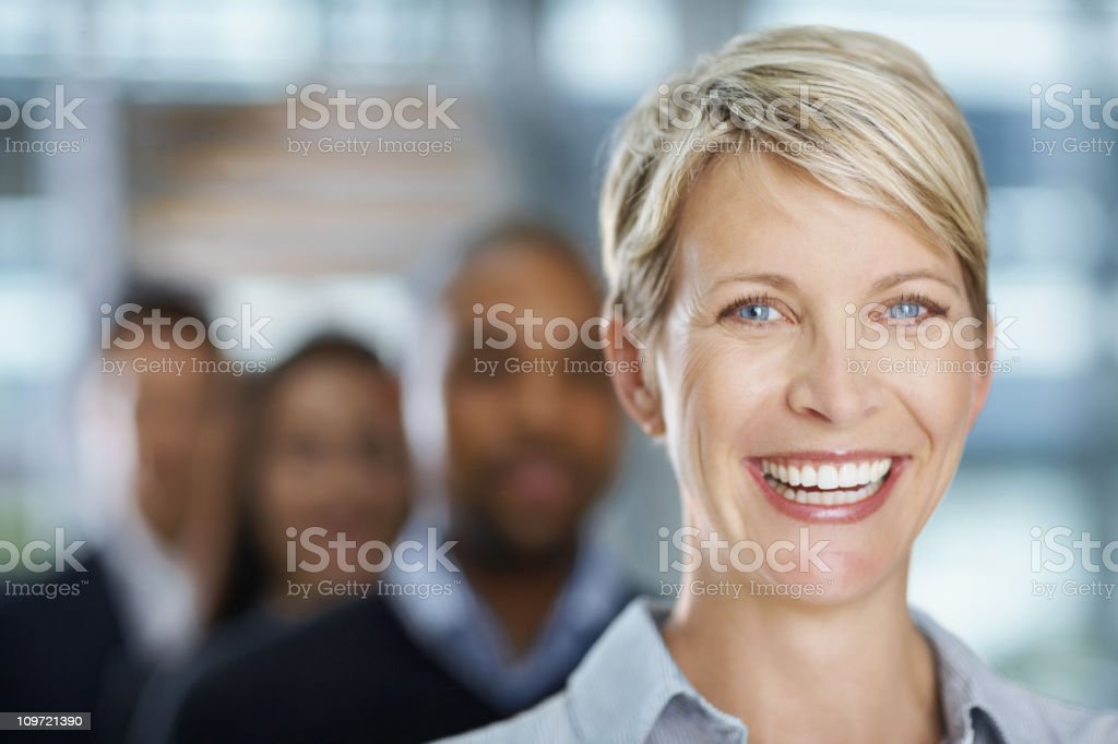 Businesswoman smiling with colleagues in the background stock photo