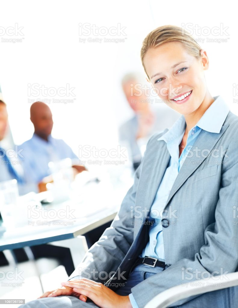 Businesswoman smiling with colleagues in the background royalty-free stock photo