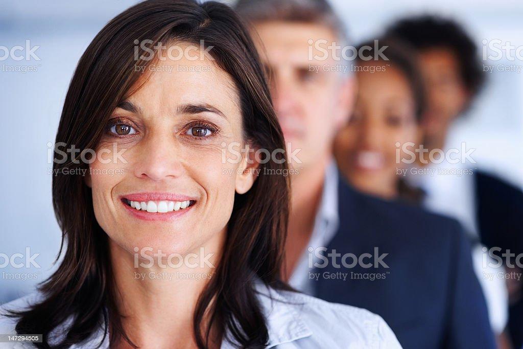 Geschäftsfrau lächelnd mit Kollegen im Hintergrund – Foto