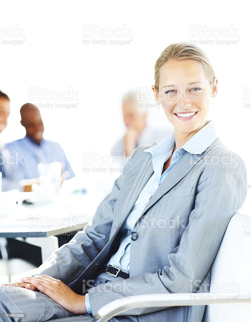 Businesswoman smiling with her colleagues in the background royalty-free stock photo