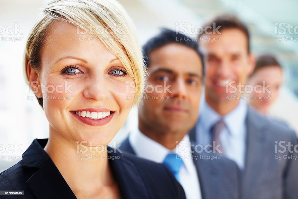 Businesswoman smiling with her team in the background royalty-free stock photo