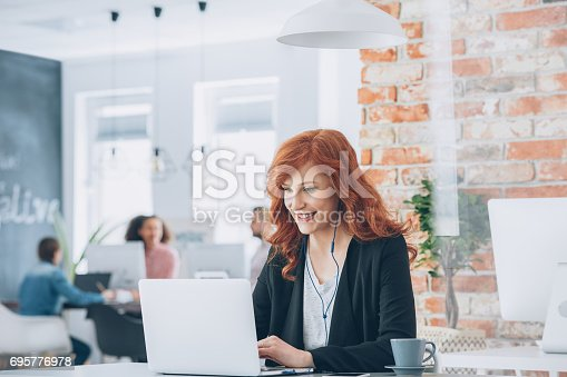 istock Businesswoman smiling working on laptop 695776978
