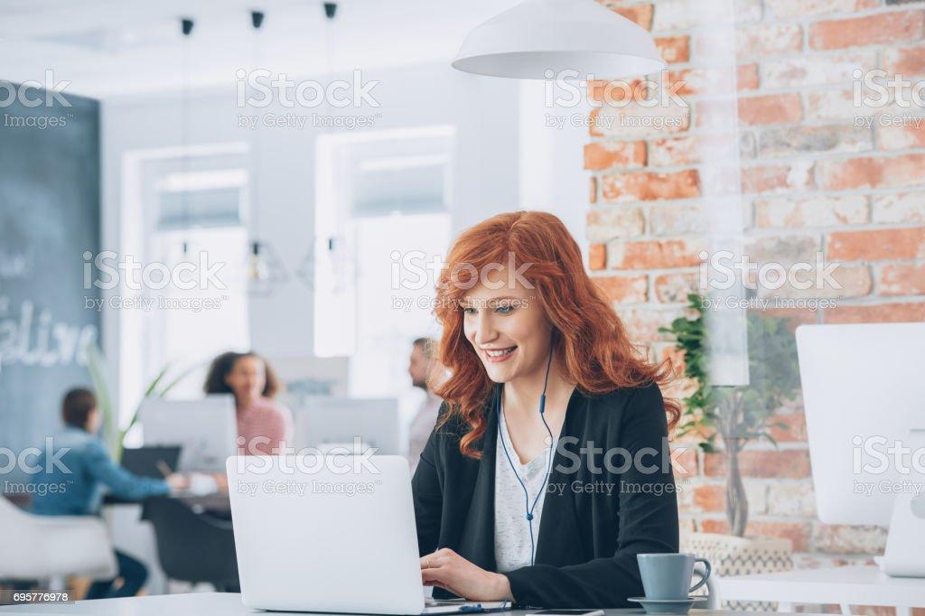 Empresaria sonriente trabajando en ordenador portátil - foto de stock