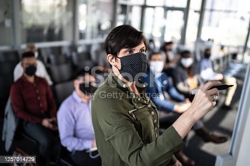Businesswoman speaking at a business conference - with face mask