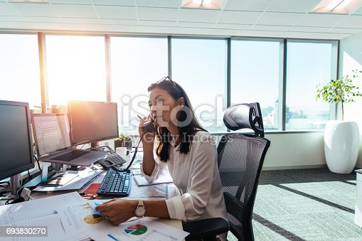 Woman entrepreneur having a business conversation on phone. Woman sitting at her desk in office working with data on charts and graphs.