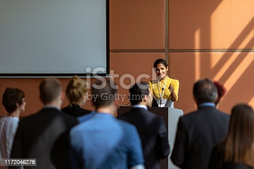 An Indian female presenter interacting with the audience at a business presentation in the board room