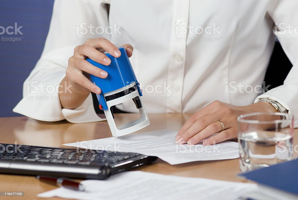 Businesswoman stamping documents royalty-free stock photo