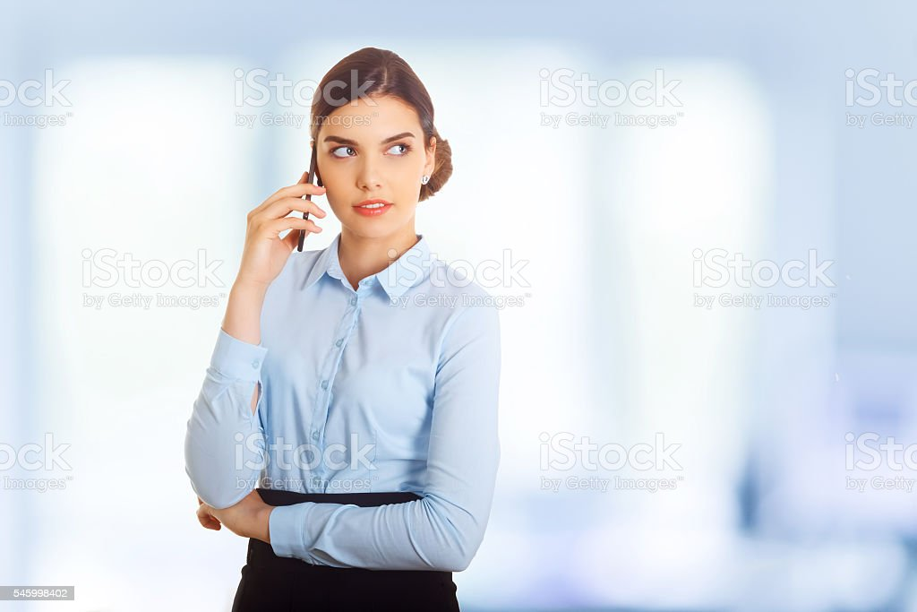 Businesswoman standing against office window talking on mobile phone stock photo