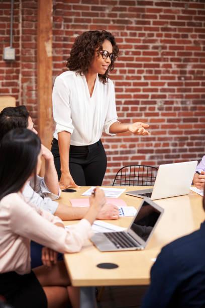 businesswoman standing and leading office meeting around table - przewodzić zdjęcia i obrazy z banku zdjęć