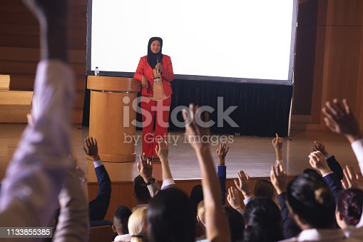 1133973551 istock photo Businesswoman standing around the podium in the auditorium 1133855385