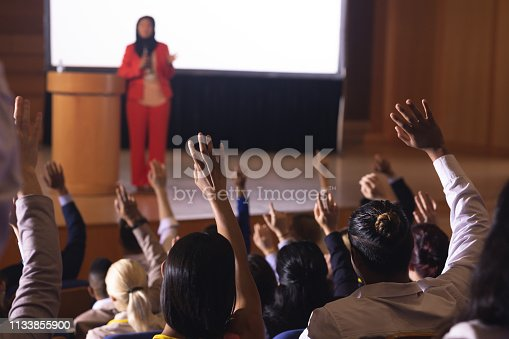1133973551 istock photo Businesswoman standing around the podium in the auditorium 1133855900