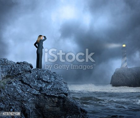 A businesswoman standing on a cliff above a rocky coastline as she looks through the fog and across the rough ocean waters towards a lighthouse high on a cliff in the distance. A beam of light emanates from the lighthouse through the fog out towards the ocean. Lots of negative space for copy.