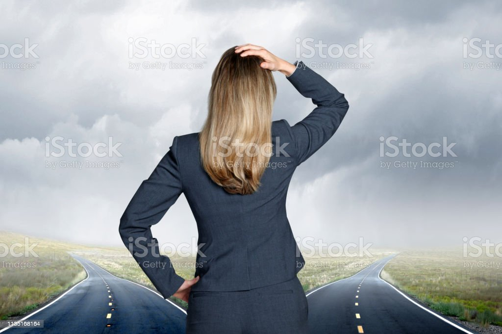 Businesswoman Standing At Fork In Road Looking Into The Distance stock photo