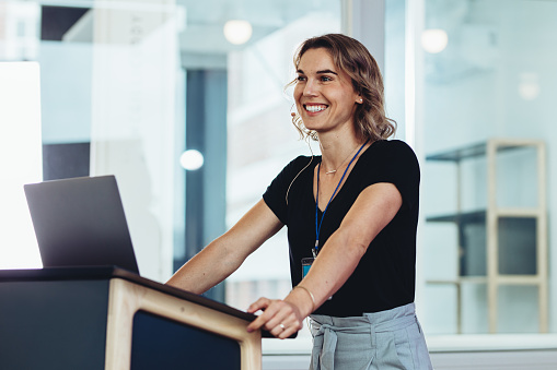Businesswoman standing at podium with laptop and smiling. Successful female business professional addressing a conference.